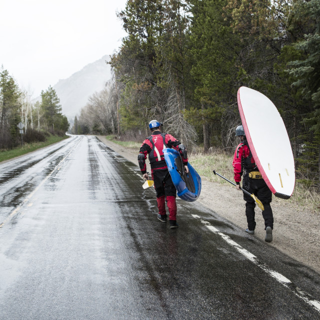 """""""Rear view of paddlers carrying paddleboards while walking on wet road"""" stock image"""