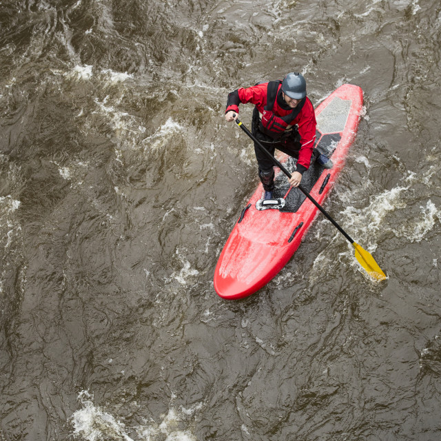 """""""High angle view of man paddleboarding in river"""" stock image"""