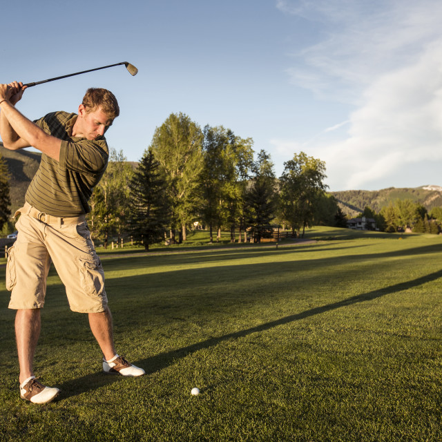 """""""Golfer swinging golf club while standing on grassy field"""" stock image"""