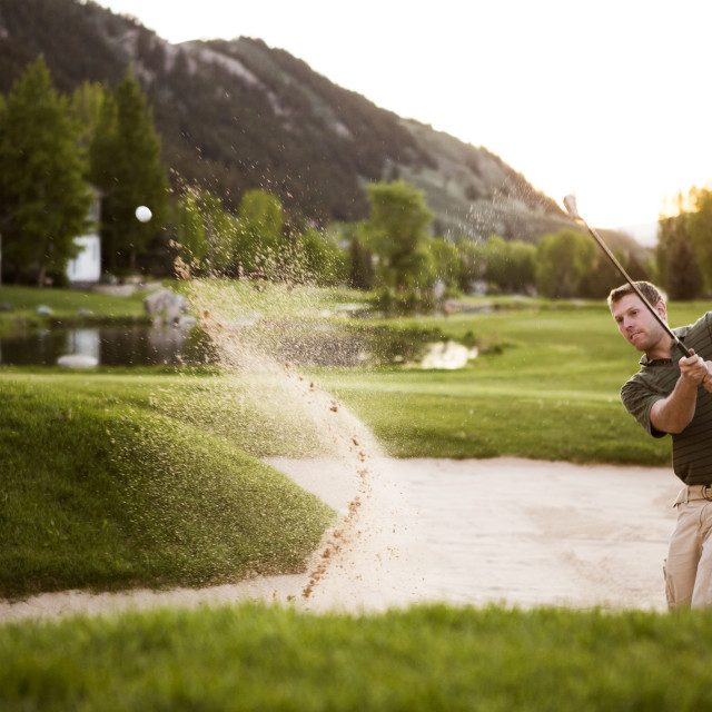 """""""Golfer hitting golf ball while standing on sand trap at field"""" stock image"""
