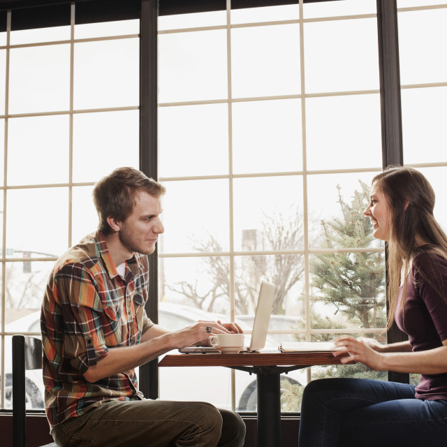 """""""Happy friends sitting at coffee shop by window"""" stock image"""