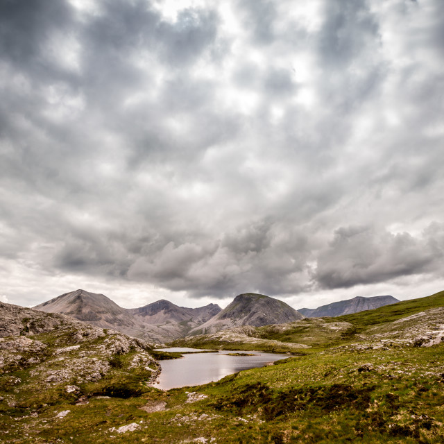 """Mountain tarn with dramatic sky"" stock image"