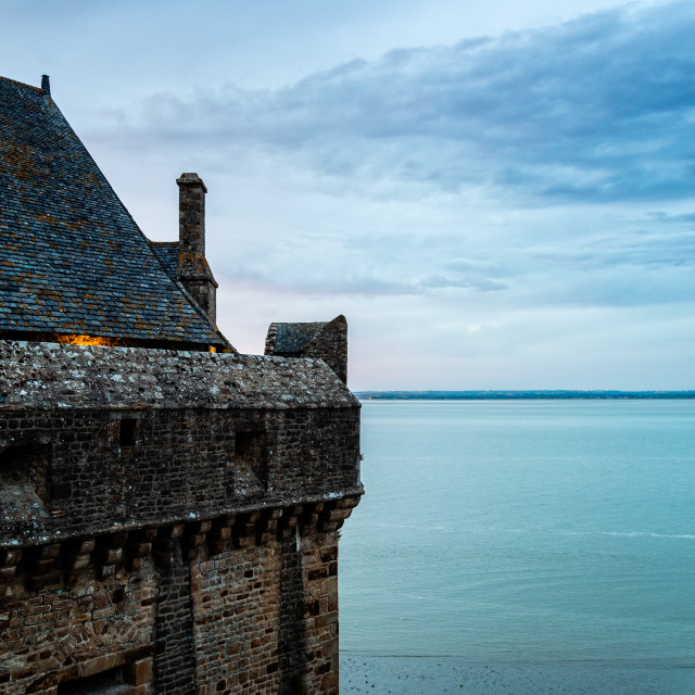 """View of the ramparts of Mont Saint Michel with the tide coming in at sunset"" stock image"
