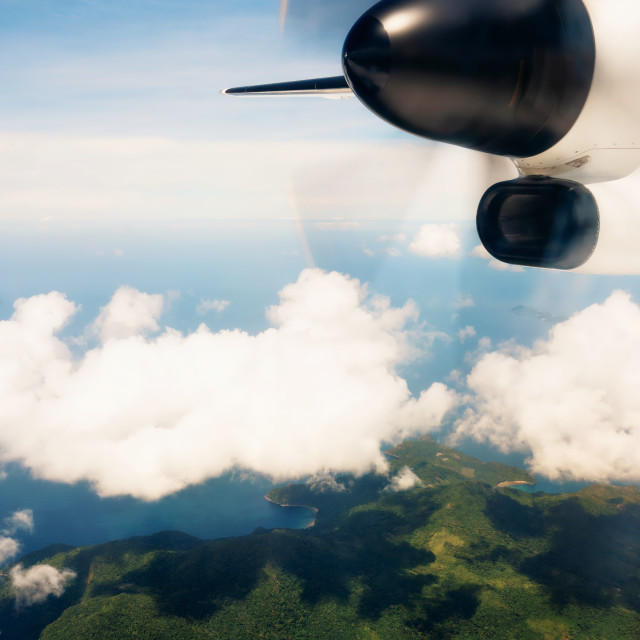 """""""Propeller aircraft wing over tropical island"""" stock image"""