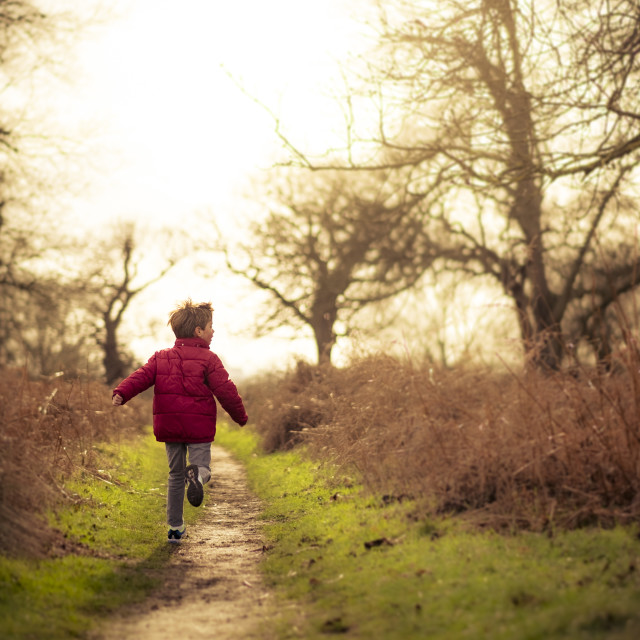 """Boy Running down path in winter sun"" stock image"