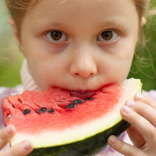 """""""cute little girl eating watermelon on the grass in summertime"""" stock image"""