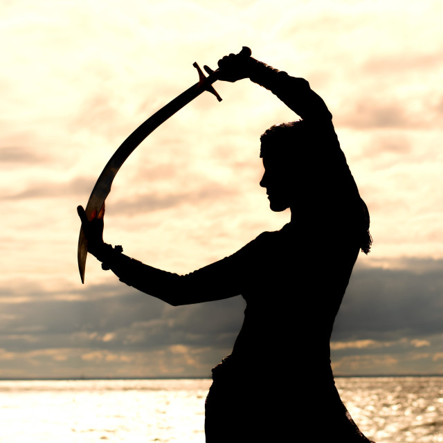 """""""Silhouette of a woman with a sword in her hands on the seashore. Feeling of motivation, strength and courage concept."""" stock image"""