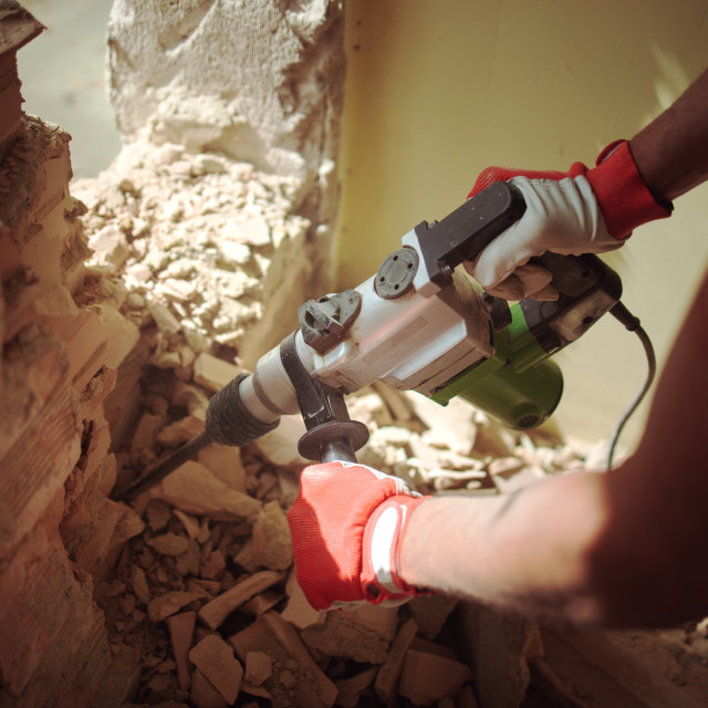 """Renovation and builder. Worker with demolition hammer breaking i"" stock image"