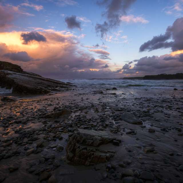 """Cloudy Twilight on a Rocky Beach"" stock image"