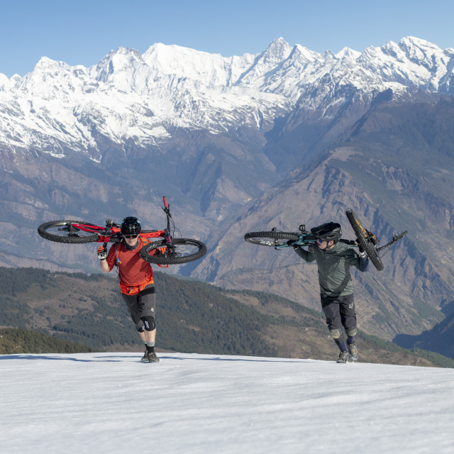 """""""Mountain bikers carry their bikes up a snow covered slope in the Himalayas..."""" stock image"""