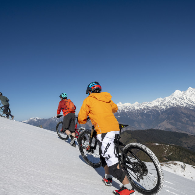 """""""Mountain bikers cycle along a snow covered slope in the Himalayas with views..."""" stock image"""