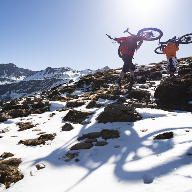 """""""Mountain bikers carry their bikes up a snow covered hillside in the Nepal..."""" stock image"""