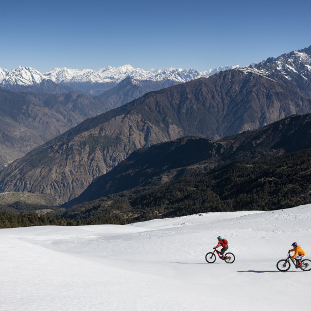 """""""Mountain bikers descend a snow covered slope in the Himalayas with views of..."""" stock image"""