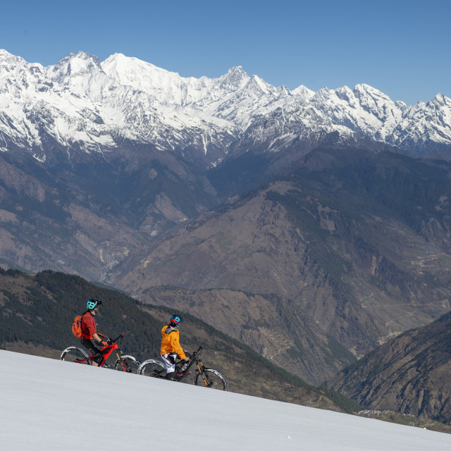 """""""Mountain biking on a snow covered slope in the Himalayas with views of the..."""" stock image"""