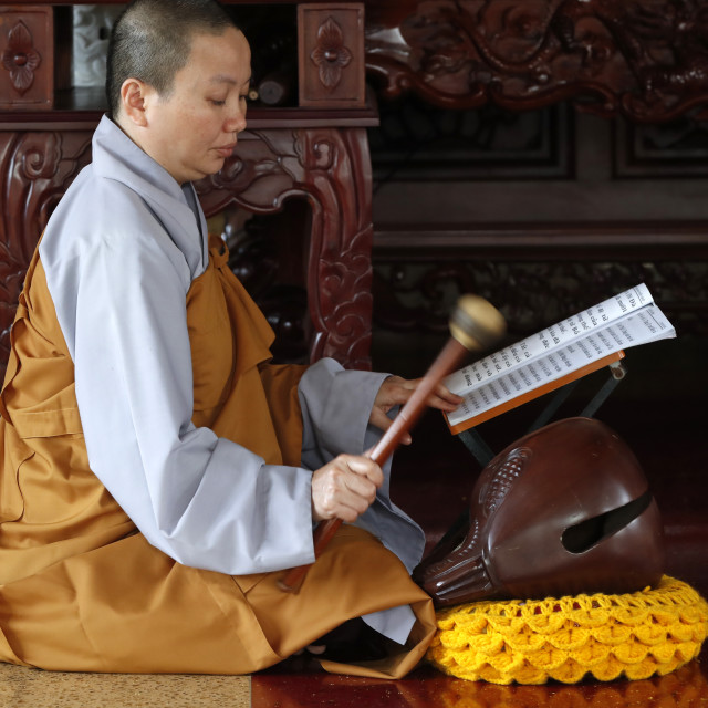 """""""Buddhist ceremony at temple. Monk playing on a wooden fish (percussion..."""" stock image"""