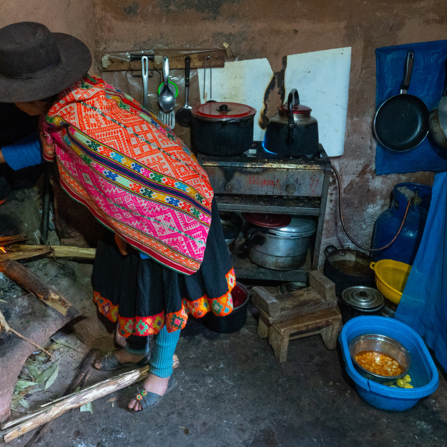 """""""Local woman in colourful traditional dress cooks breakfast over an open fire,..."""" stock image"""