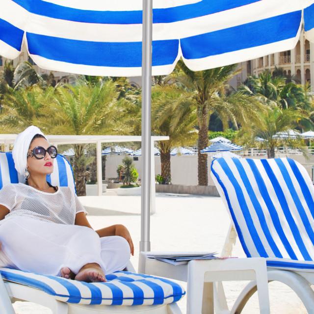 """Woman relaxing under a beach umbrella."" stock image"
