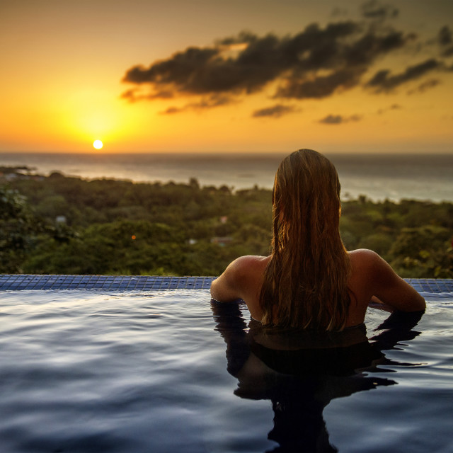 """""""Woman looking at sunset from a pool, Roatan, Caribbean"""" stock image"""