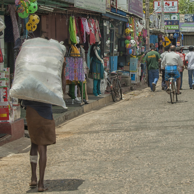 """Man carrying heavy bag on the streets of Trincomalee in Sri Lank"" stock image"