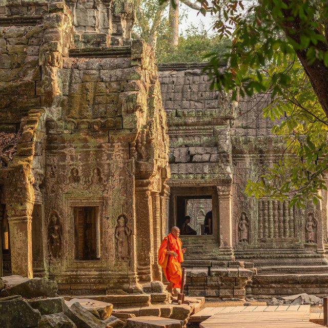 """A lone monk walking through the Buddhist temple of Ta Prohm within the Angkor..."" stock image"