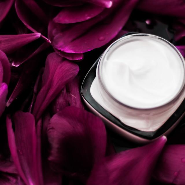 """Sensitive skincare moisturizer cream on purple flower petals background,..."" stock image"