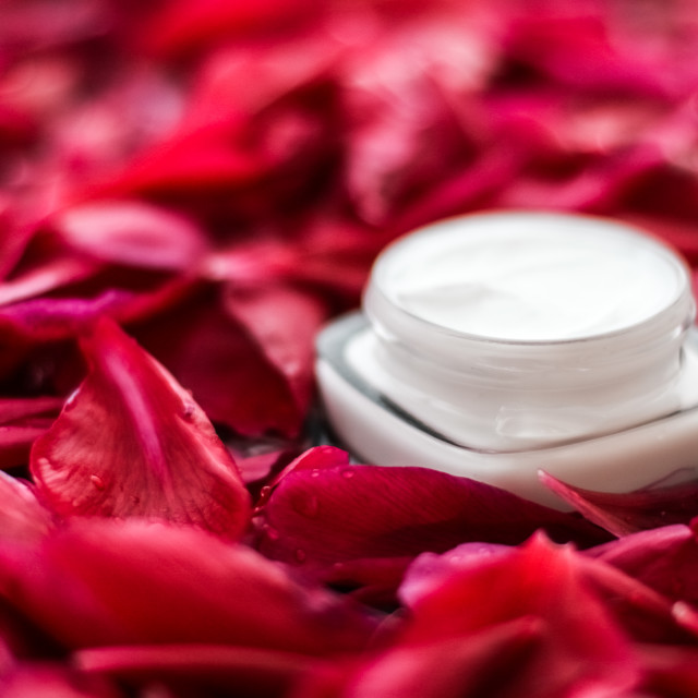 """""""Sensitive skincare moisturizer cream on red flower petals and water..."""" stock image"""