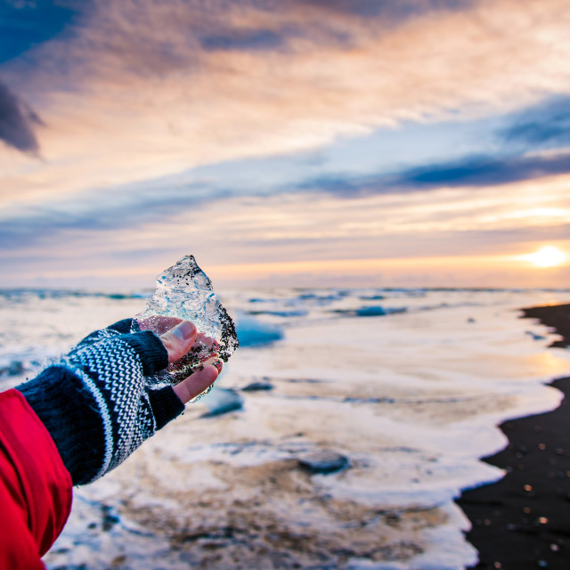 """Traveler holding ice chunk on Diamond beach in Iceland"" stock image"