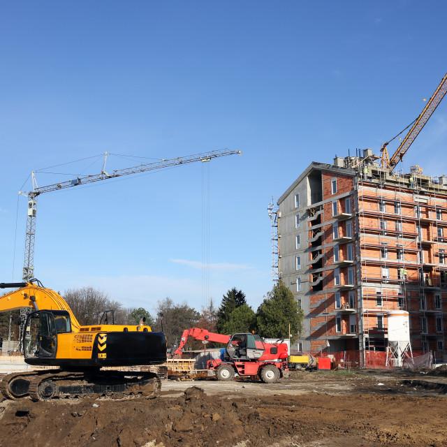 """excavators and cranes on construction site"" stock image"