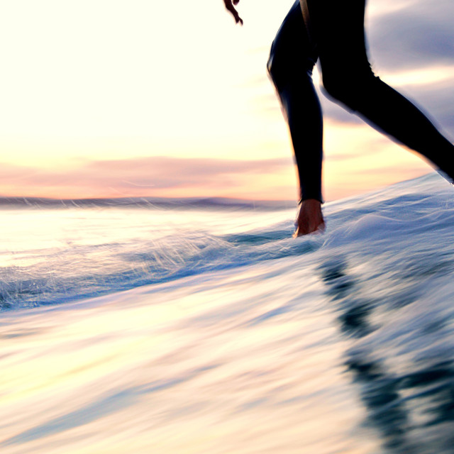 """""""Slow shutter - Longboarder cross stepping up a surfboard at sunset"""" stock image"""