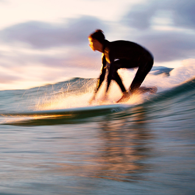 """""""Slow shutter - Longboarder popping up on a smooth wave at sunset - Gold Coast"""" stock image"""