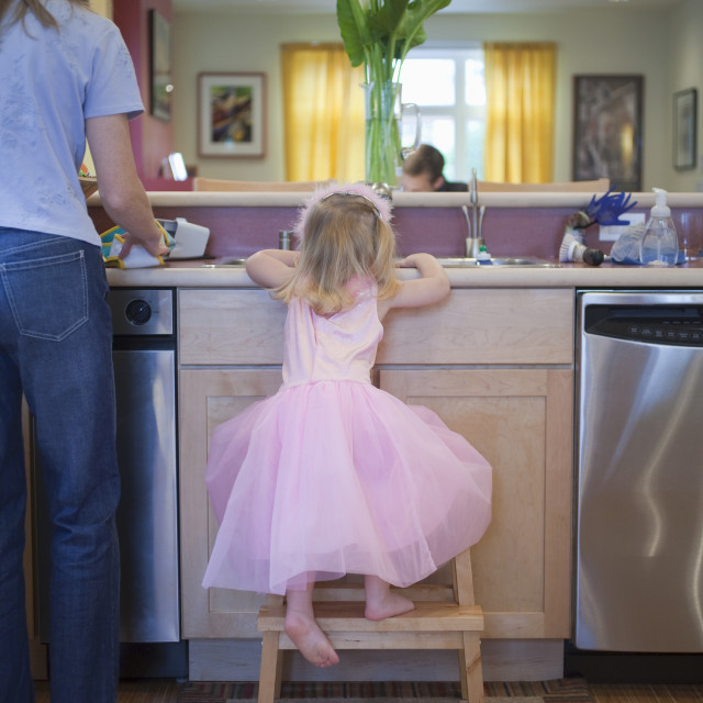 """""""Girl with her mother in the kitchen of a disability accessible home"""" stock image"""
