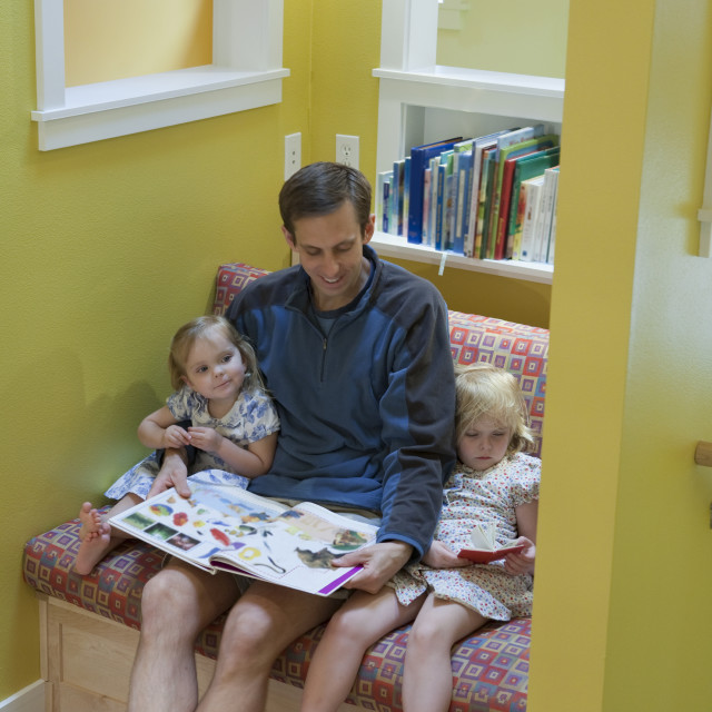"""""""Girls reading with their father in sitting room of a disability accessible home"""" stock image"""