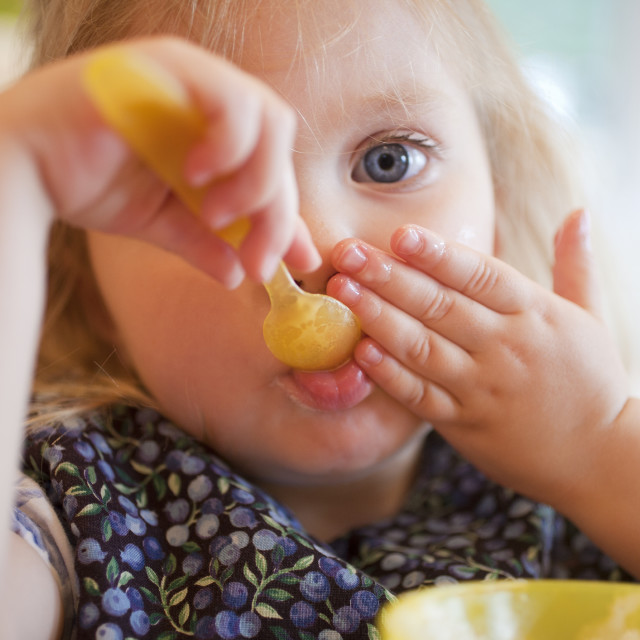 """""""Girl feeding herself in a disability accessible home"""" stock image"""