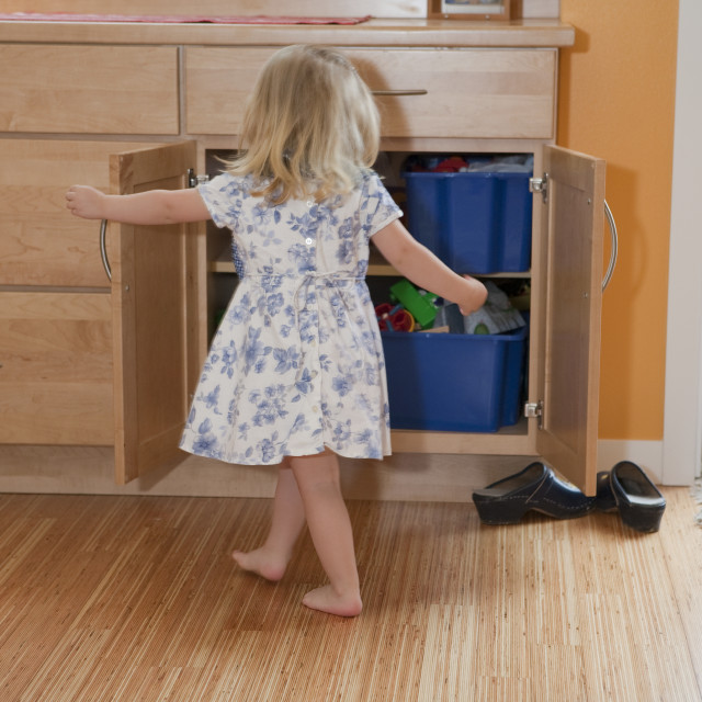 """""""Girl searching in a closet of a disability accessible home"""" stock image"""