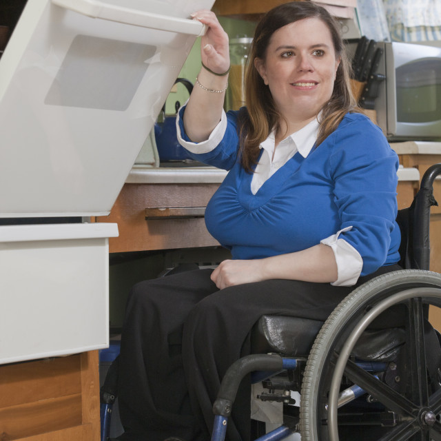"""""""Woman with Spina Bifida in a wheelchair using a stove in the accessible kitchen"""" stock image"""