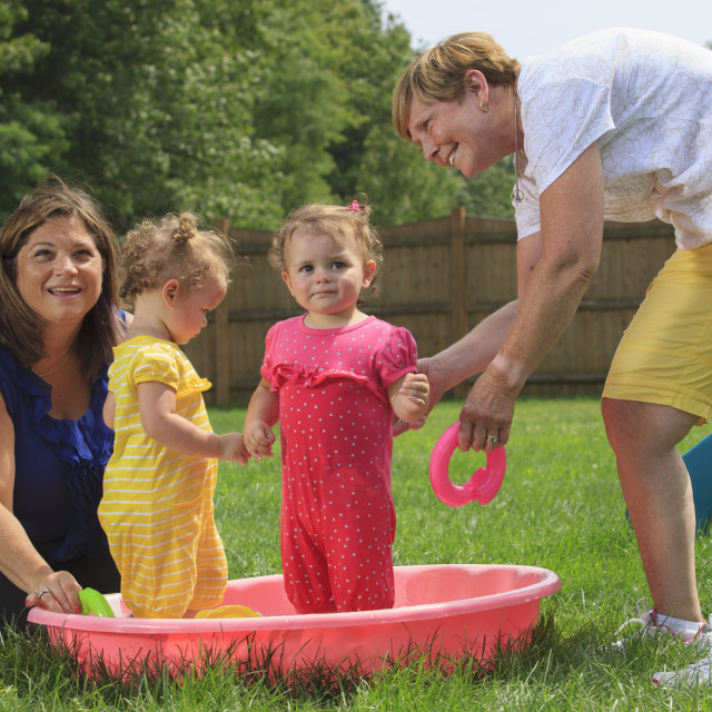 """""""Grandmother with a prosthetic leg playing with her grandchildren on a child's..."""" stock image"""