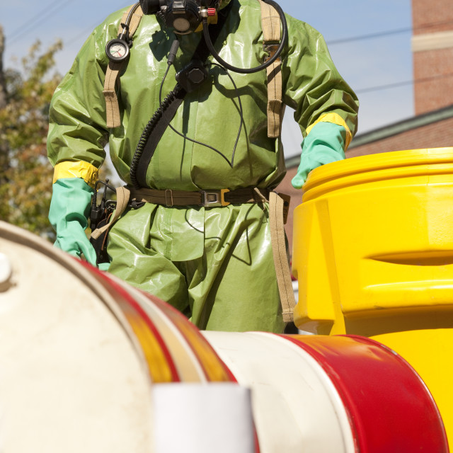 """HazMat firefighter pushing a salvage drum"" stock image"