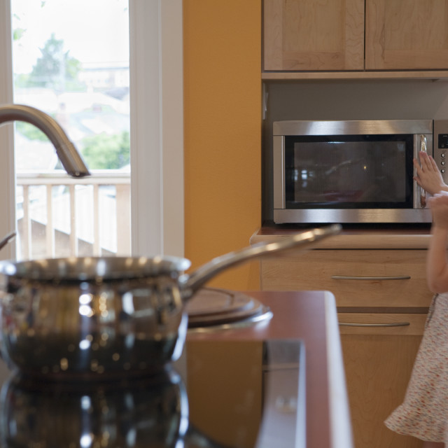 """""""Girl using a microwave in a disability accessible home"""" stock image"""