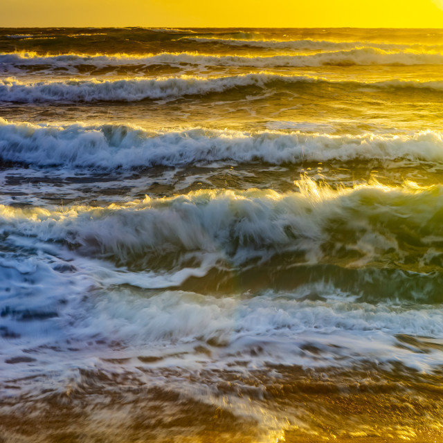 """""""Waves of the Pacific Ocean reflecting golden sunlight at sunrise off the..."""" stock image"""