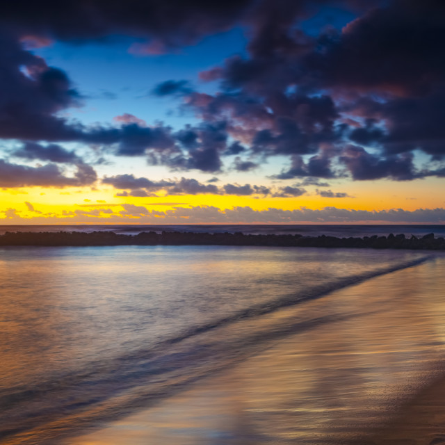 """""""Dramatic sunrise over Lydgate Park, breakwater and the ocean from the coast..."""" stock image"""