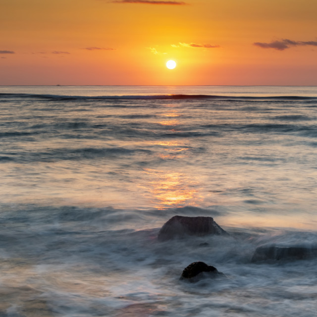"""""""Sinking sun over the horizon of the ocean with soft rolling waves; Kauai,..."""" stock image"""