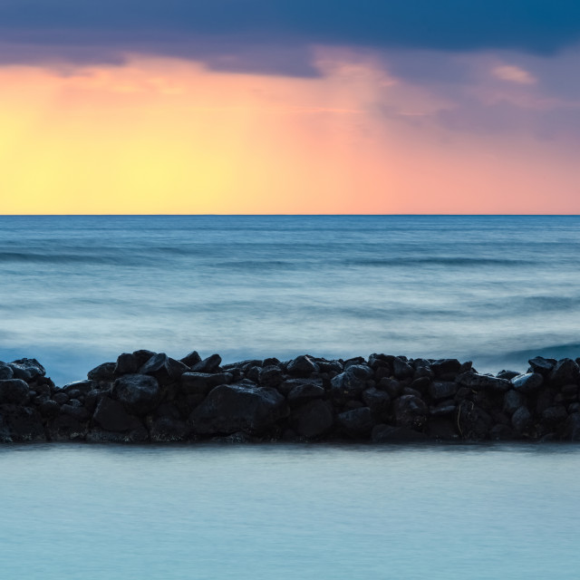 """""""Warm sunrise over Lydgate Beach, breakwater and the ocean from the coast of..."""" stock image"""