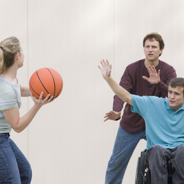 """""""Young man sitting in a wheelchair and playing basketball."""" stock image"""