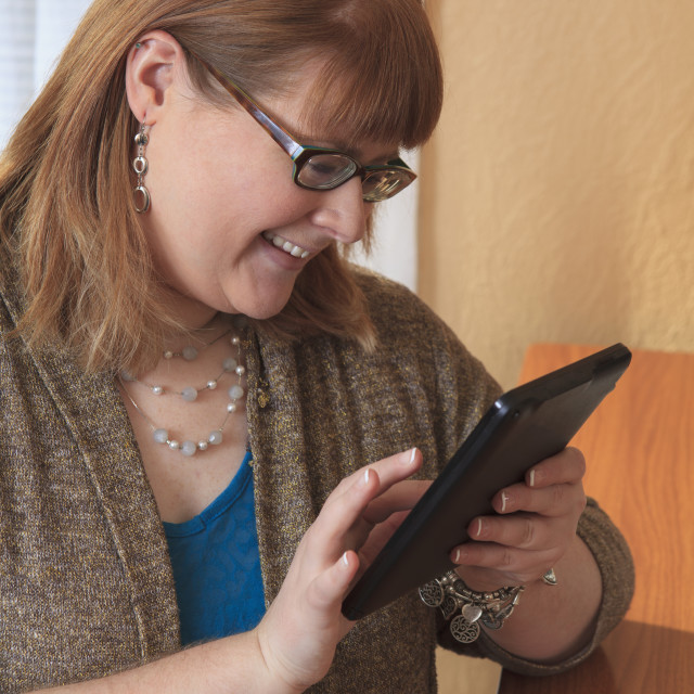 """""""Woman who is legally blind using her tablet in her home"""" stock image"""