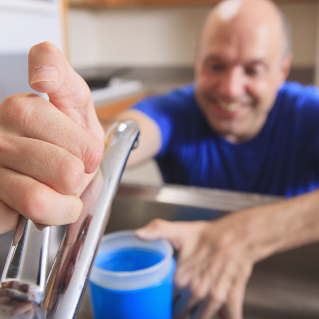 """""""Man with Friedreich's Ataxia and deformed hands using his faucet in the kitchen"""" stock image"""