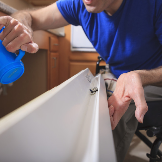 """""""Man with Friedreich's Ataxia and deformed hands using his dishwasher"""" stock image"""