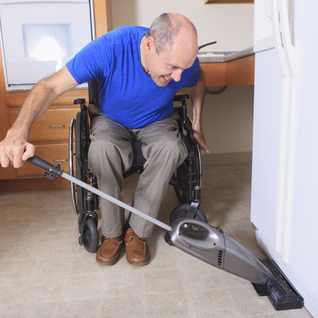 """""""Man with Friedreich's Ataxia and deformed hands vacuuming his house from his..."""" stock image"""