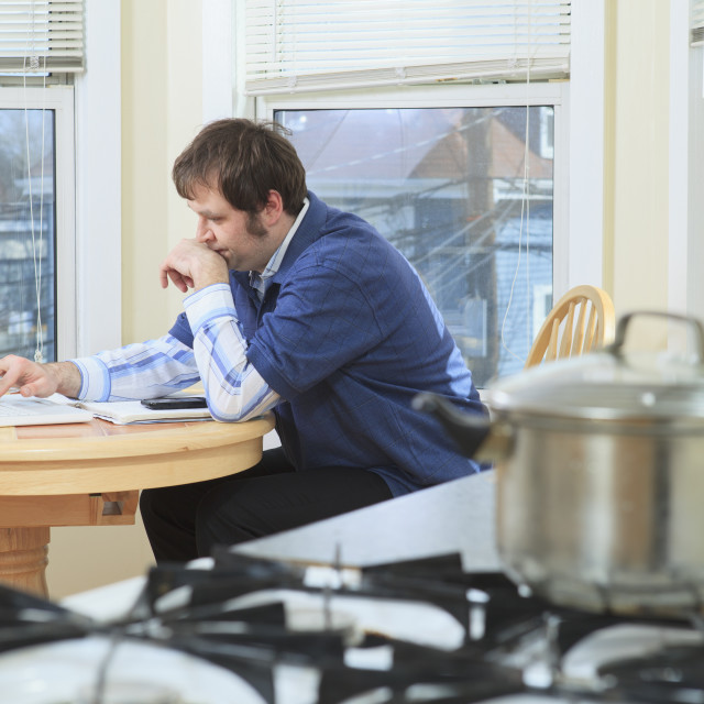 """""""Man with Asperger's working in his home while cooking"""" stock image"""