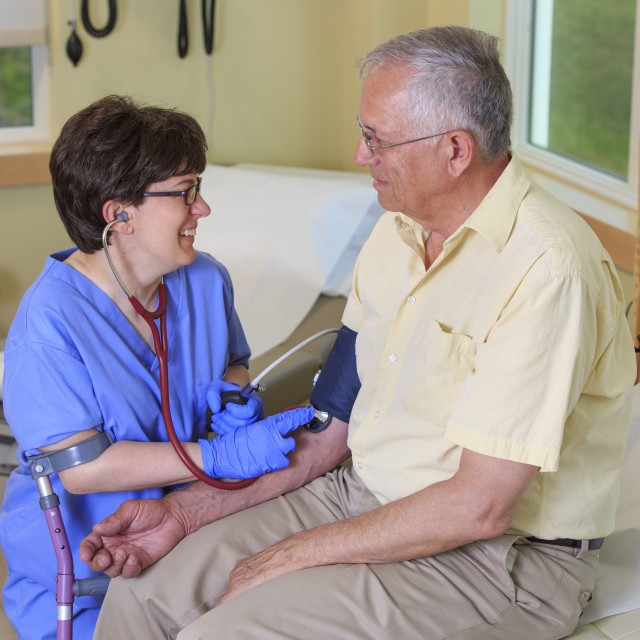 """""""Nurse with Cerebral Palsy taking a patient's blood pressure in a clinic"""" stock image"""