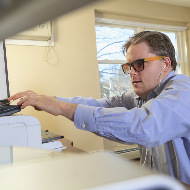 """""""Man with congenital blindness scanning paperwork at his computer"""" stock image"""